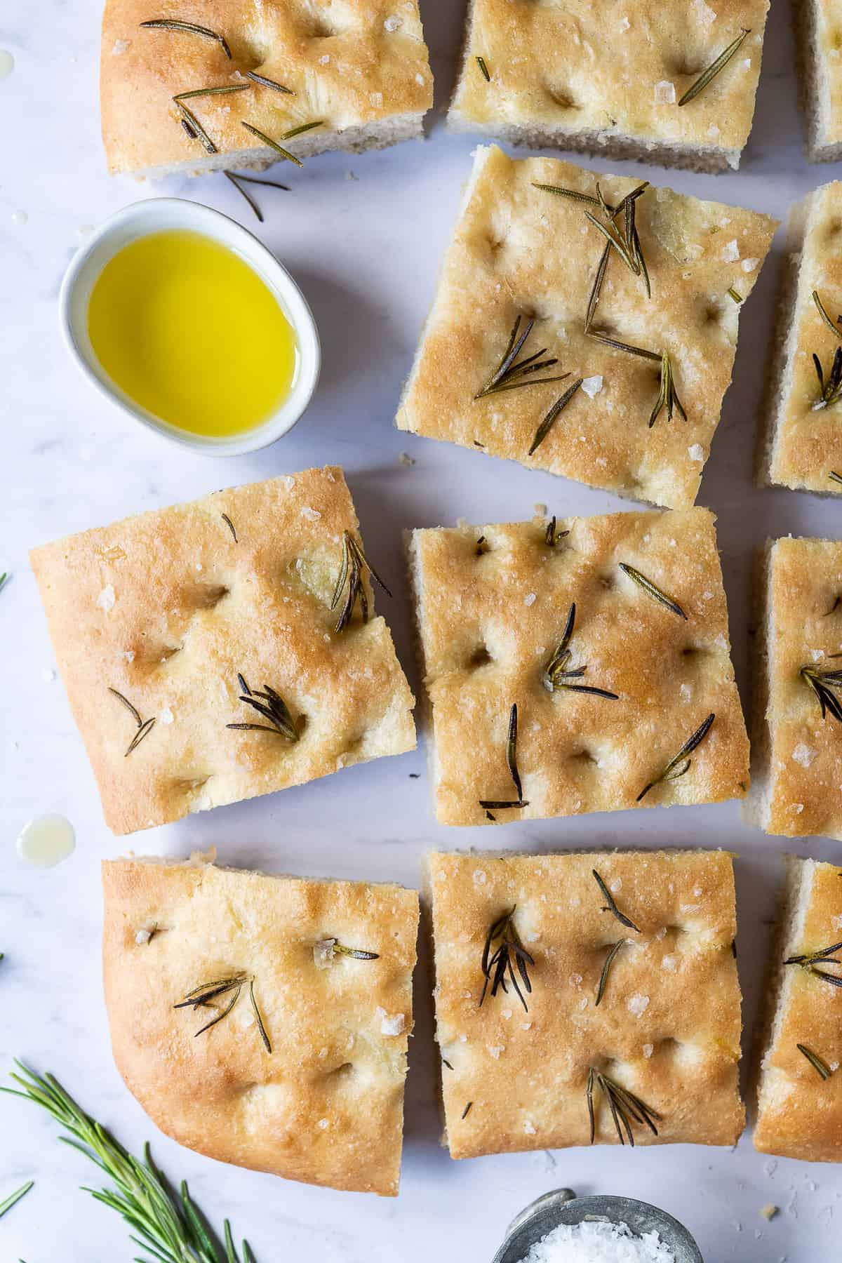 Squares of sea salt and rosemary focaccia with a bowl of olive oil.