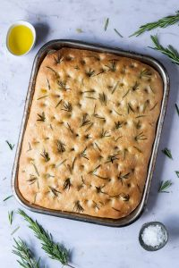 Loaf of sea salt and rosemary focaccia in a baking tin on a marble background with fresh rosemary and bowls of olive oil and sea salt.
