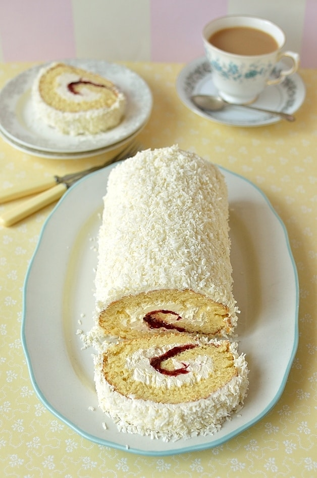 Coconut & cherry swiss roll cake, a light, fatless sponge filled with cherry jam & coconut swiss meringue buttercream, topped with desiccated coconut, this is the perfect cake for Easter.