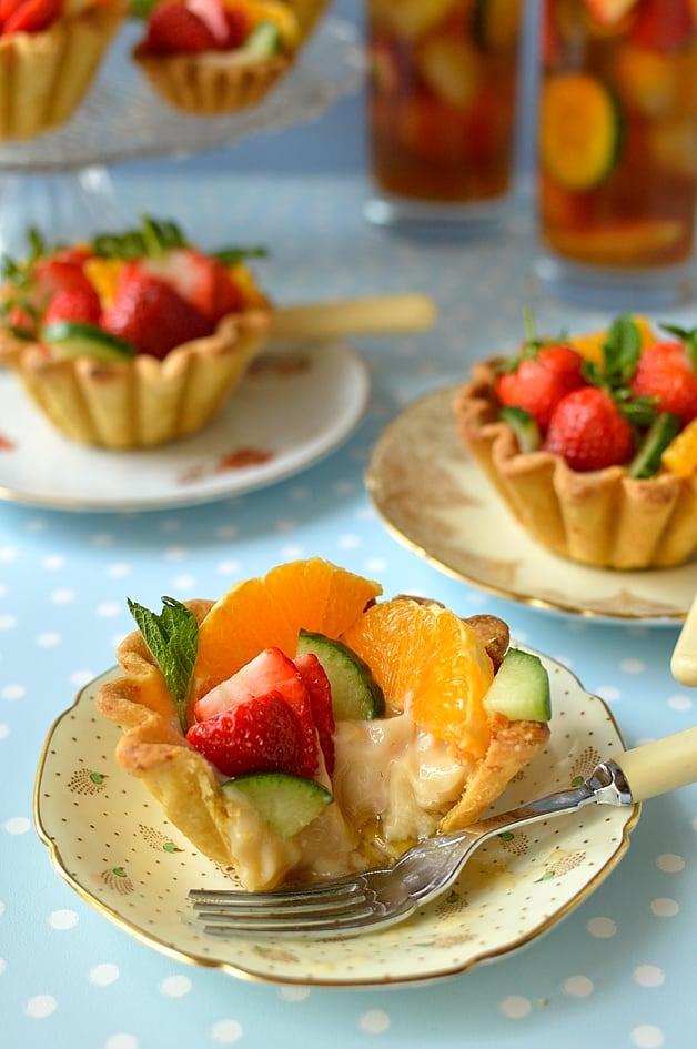 Pimm's cup fruit tarts - citrus shortcrust pastry filled with Pimm's creme patissiere, cucumber & mint jam, strawberries, orange & apple