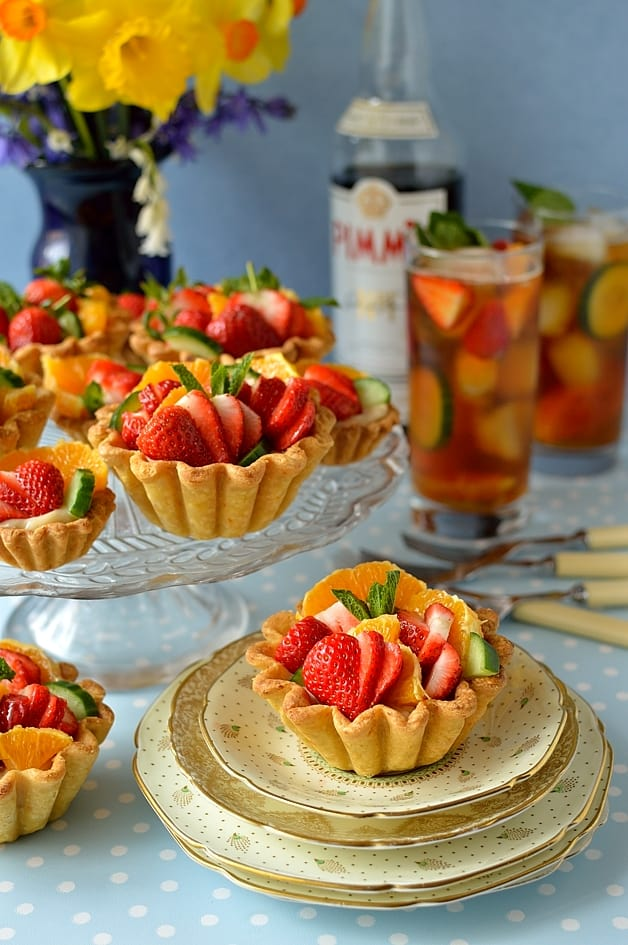 Pimm's fruit tarts - crisp citrus shortcrust pastry filled with Pimm's creme patissiere, cucumber & mint jam, strawberries, orange & apple