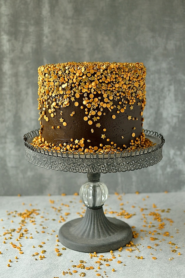 American style vanilla white cake dyed turquiose with fudgy chocolate buttercream & a cascade of gold sprinkles
