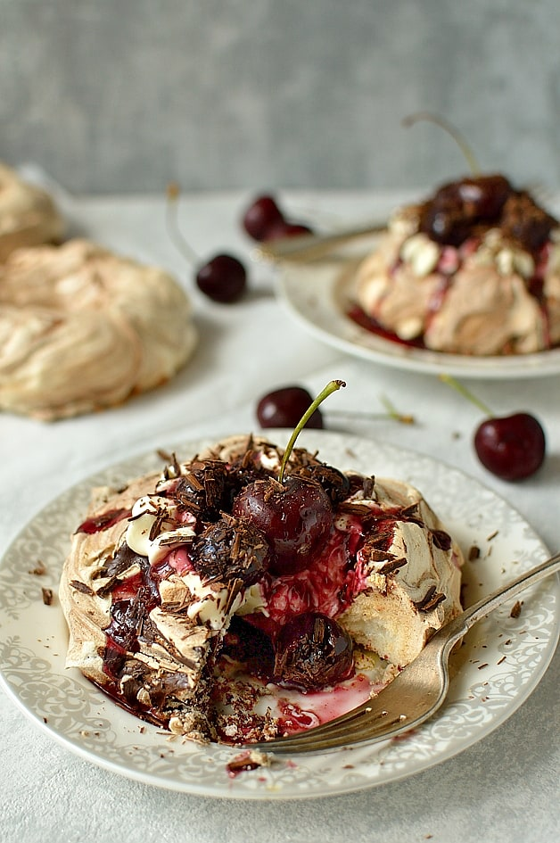 Black forest meringue nests - chocolate swirl meringues with vanilla quark whipped cream, cherry compote & chocolate shavings