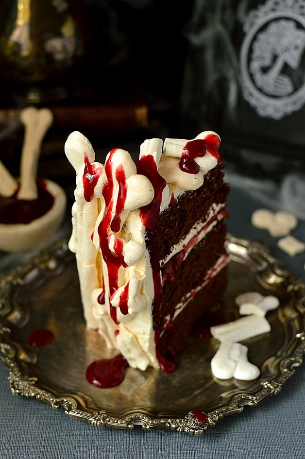 Spooky meringue bone palace Halloween cake - moist chocolate cake with vanilla swiss meringue buttercream, raspeberry jam, meringue bones and berry coulis 'blood'