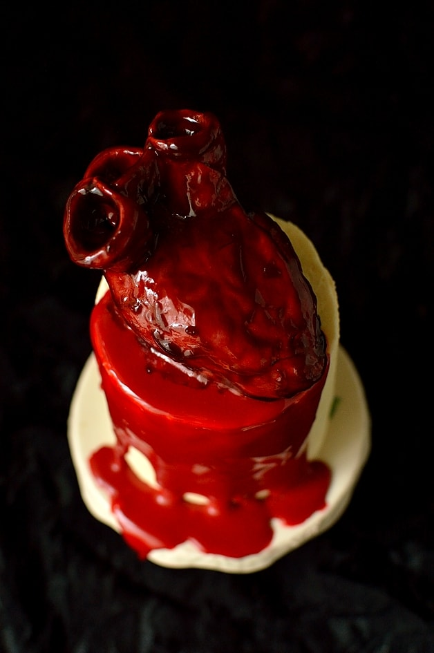 realistic bleeding heart cakes on top of mini red velvet layer cakes with ganache 'blood'