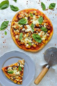 Double pumpkin goats cheese pizza - pumpkin puree in the pizza bread dough, topped with roasted pumpkin and red onion, tomato sauce, mozzarella and goats cheese