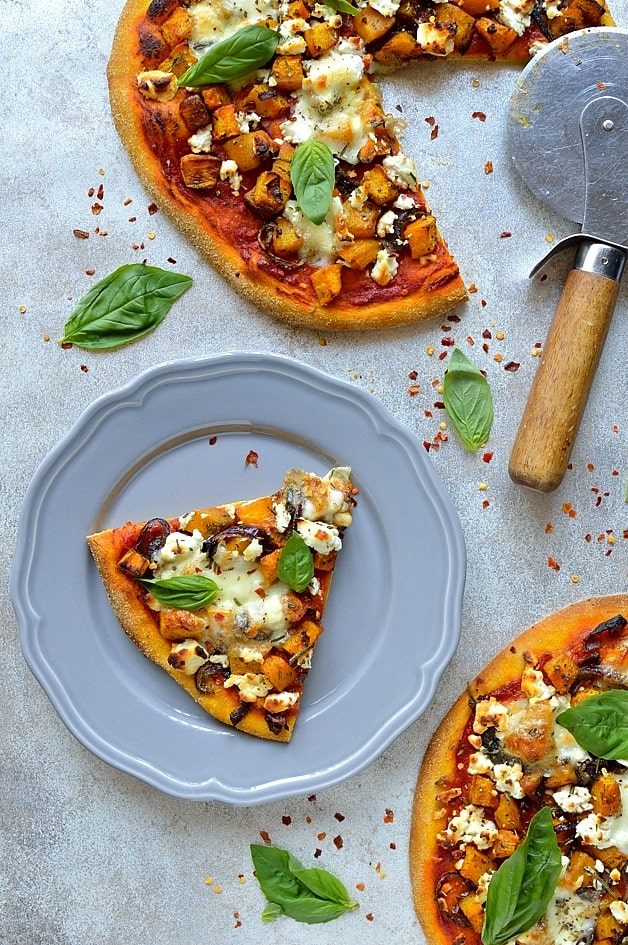 Double pumpkin goats cheese pizza made with pumpkin puree in the pizza dough, and roasted pumpkin on top, along with tomato sauce, mozzarella, goats cheese and fresh herbs