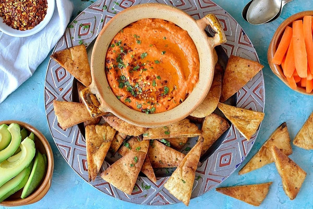 Roasted red pepper and chili hummus with home-made seasoned pitta chips. Easy to make and the perfect snack!