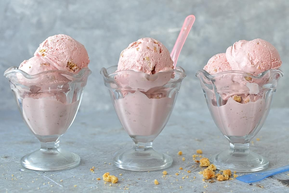 Roasted rhubarb and strawberry crumble ice cream - a delicious fruity ice cream filled with chunks of buttery crumble and topped with a tangy rhubarb strawberry sauce.