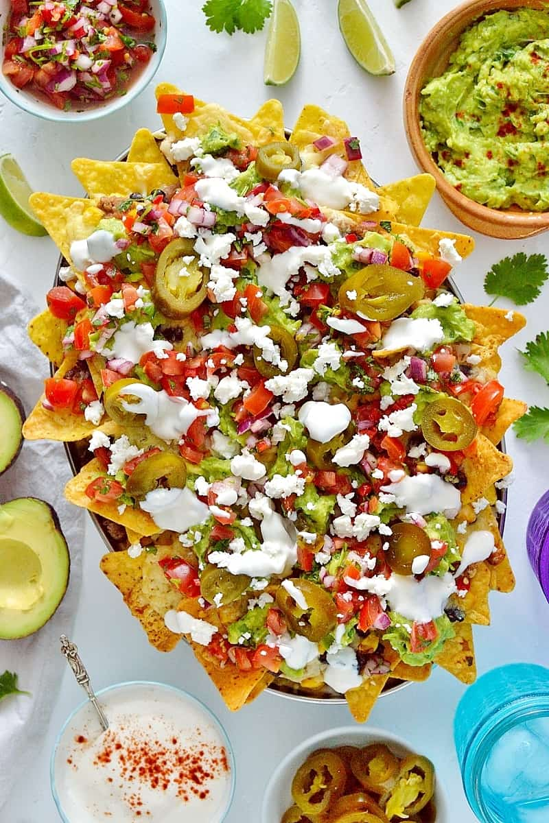 Loaded veggie nachos - topped with two kinds of beans, corn, salsa, guacamole, cheese and sour cream, this is the best way to eat a bag of chips for dinner!