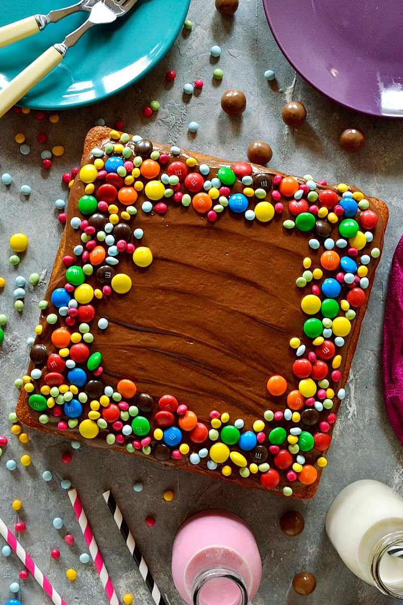 Yellow vanilla cake with chocolate ganache frosting - moist, tender yellow vanilla sheet cake with whipped chocolate ganache and M&M's.