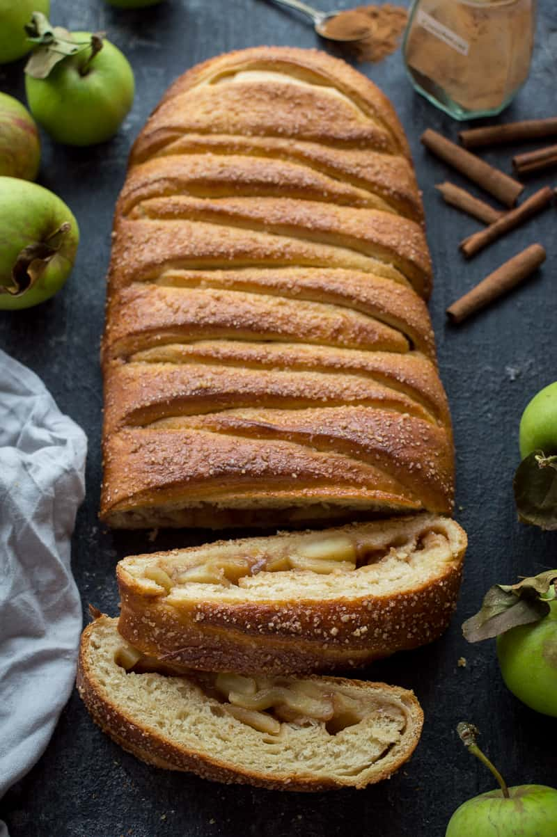 Angled shot of apple cinnamon brioche with apples and cinnamon sticks.