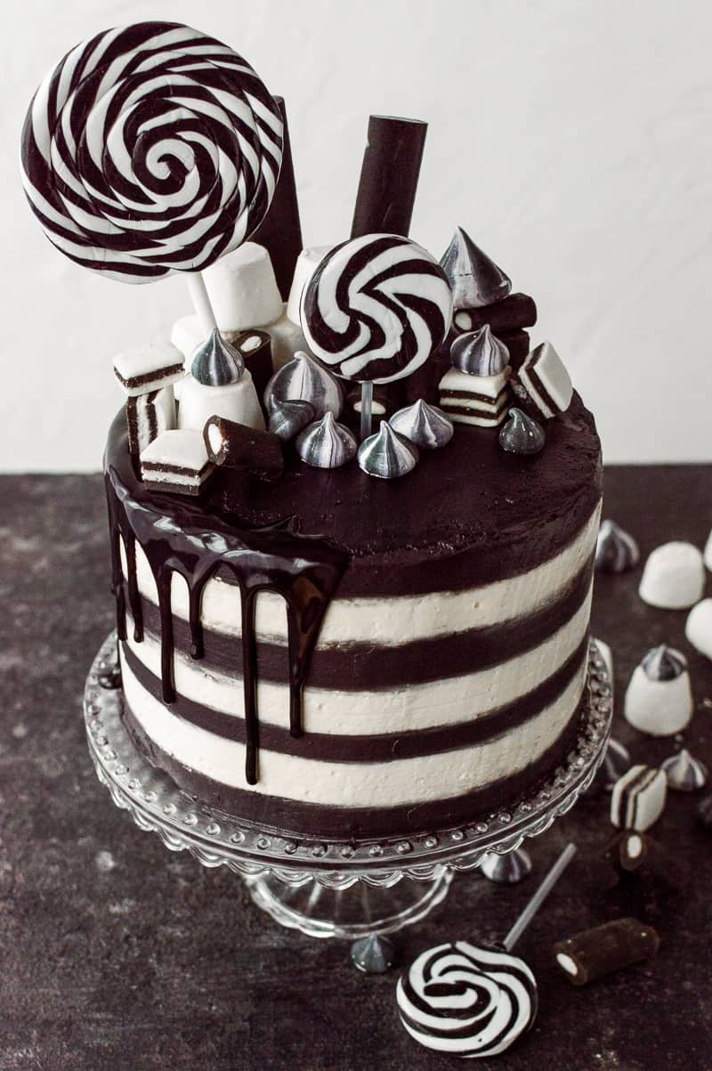 Black and white sriped cake topped with black and white sweets.