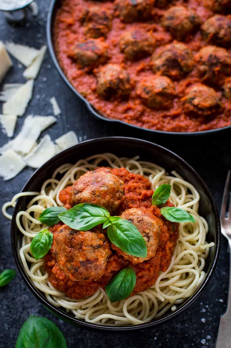 Vegetarian mushroom meatballs, tomato ragu sauce and spaghetti in a black bowl with basil leaves