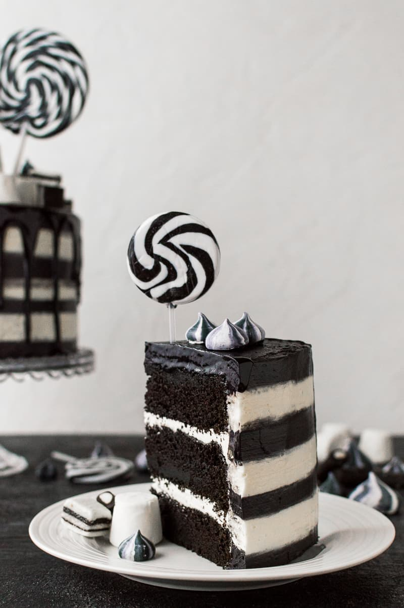 A slice of black and white striped chocolate and vanilla cake topped with a lollipop.