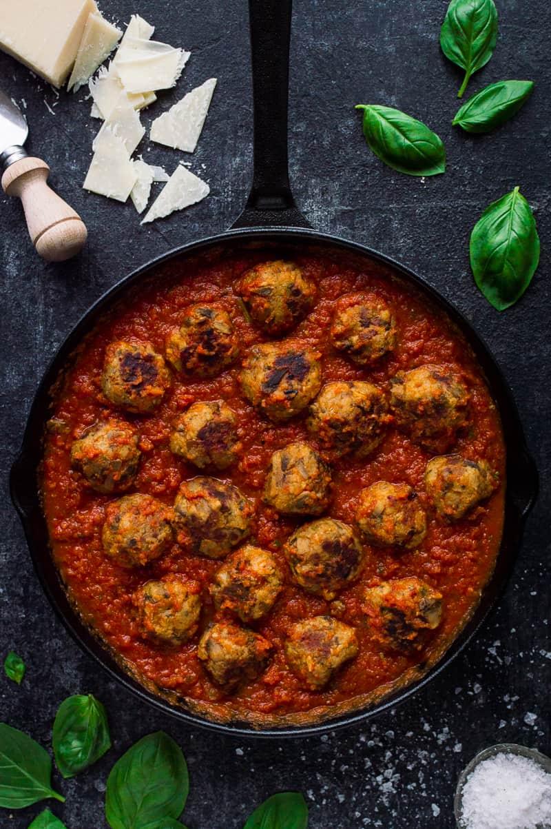 Vegetarian mushroom meatballs with tomato ragu sauce in a black skillet