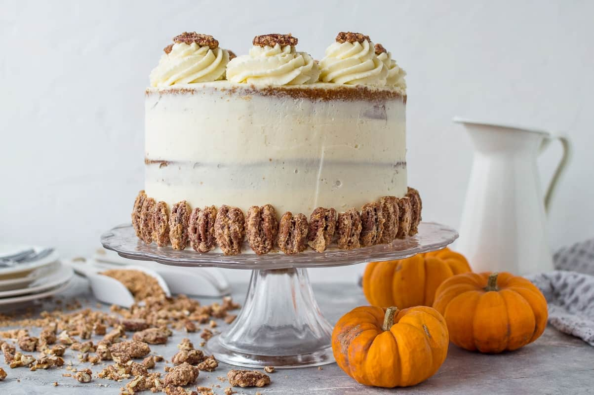 Landscape shot of pumpkin spice layer cake topped with mascarpone cream and spiced sugared pecan nuts.