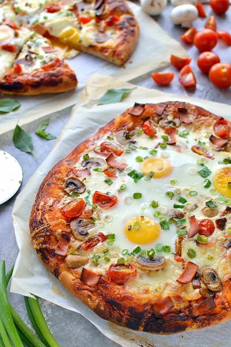 Angled shot of breakfast pizza topped with eggs, cheese, mushrooms, tomatoes, spring onions and vegetarian bacon