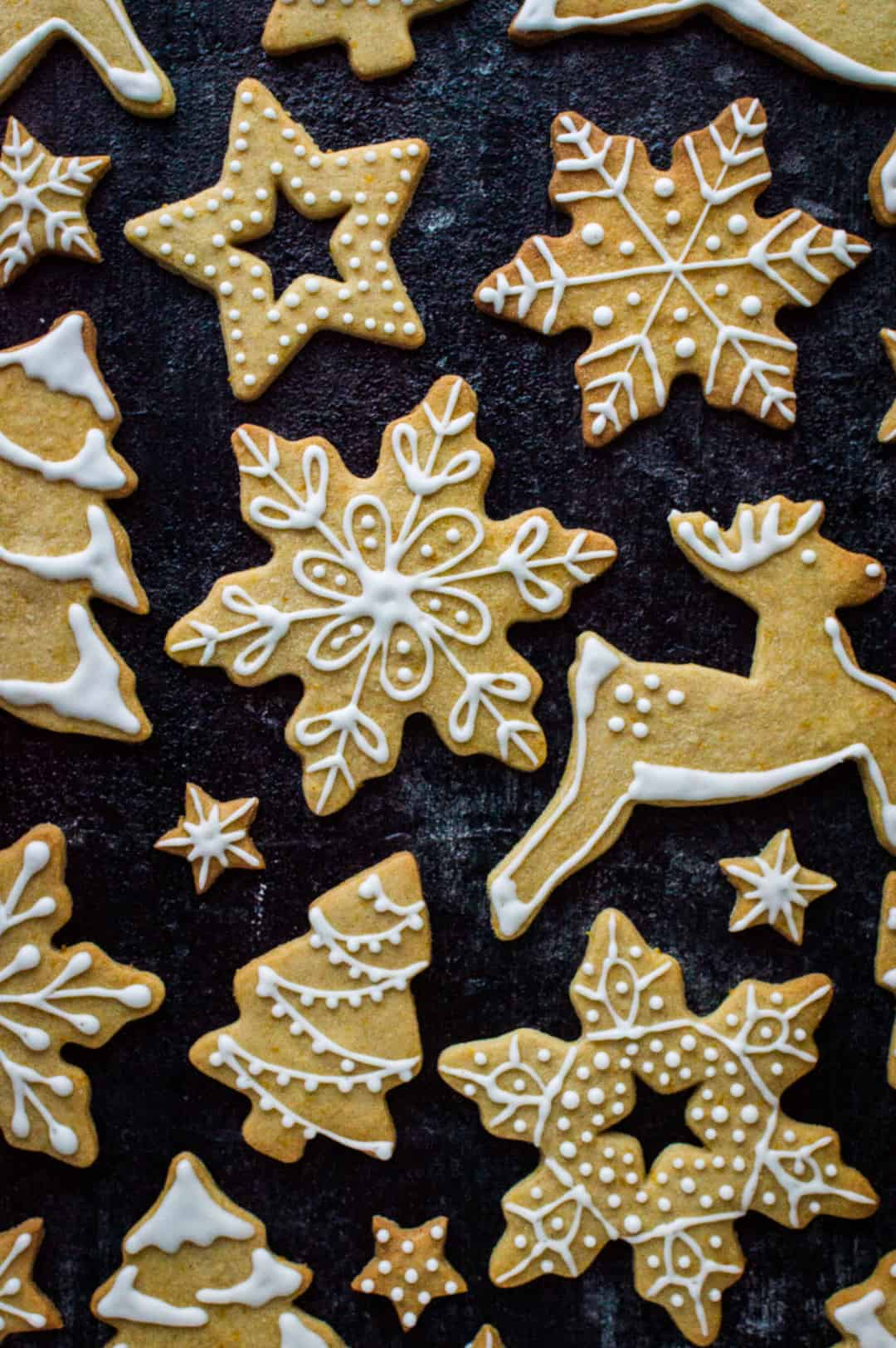 Orange and cinnamon butter cookies in reindeer, christmas tree, snowflake and star designs with white royal icing decorations