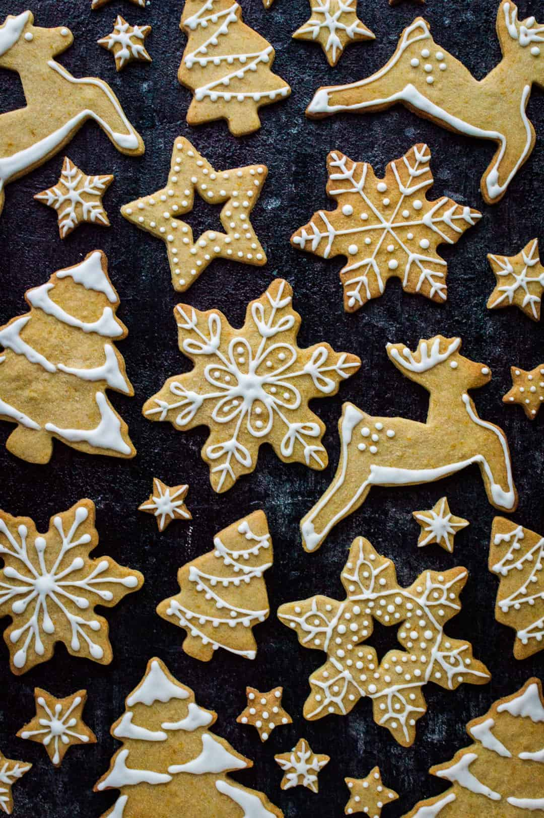 Top down shot of orange cinnamon butter biscuits in reindeer, Christmas tree, star and snowflake shapes