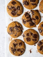 Vegan pumpkin chocolate chip cookies on a sheet of baking parchment on a grey backdrop.