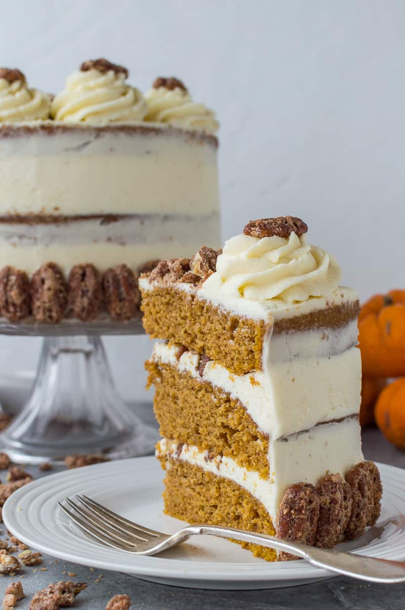 Side shot of a slice of pumpkin layer cake topped with mascarpone cream and spiced candied pecans.