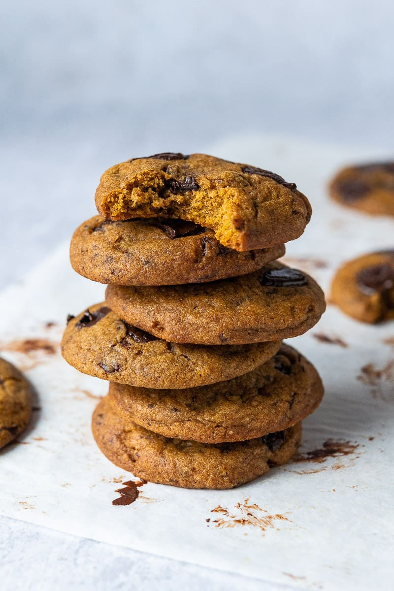 A stack of vegan pumpkin chocolate chip cookies on a grey background.