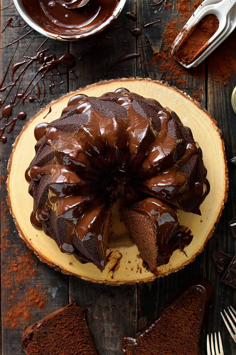 Flatlay of sliced double chocolate bundt cake on a wooden board with ganache drizzle and cocoa powder.