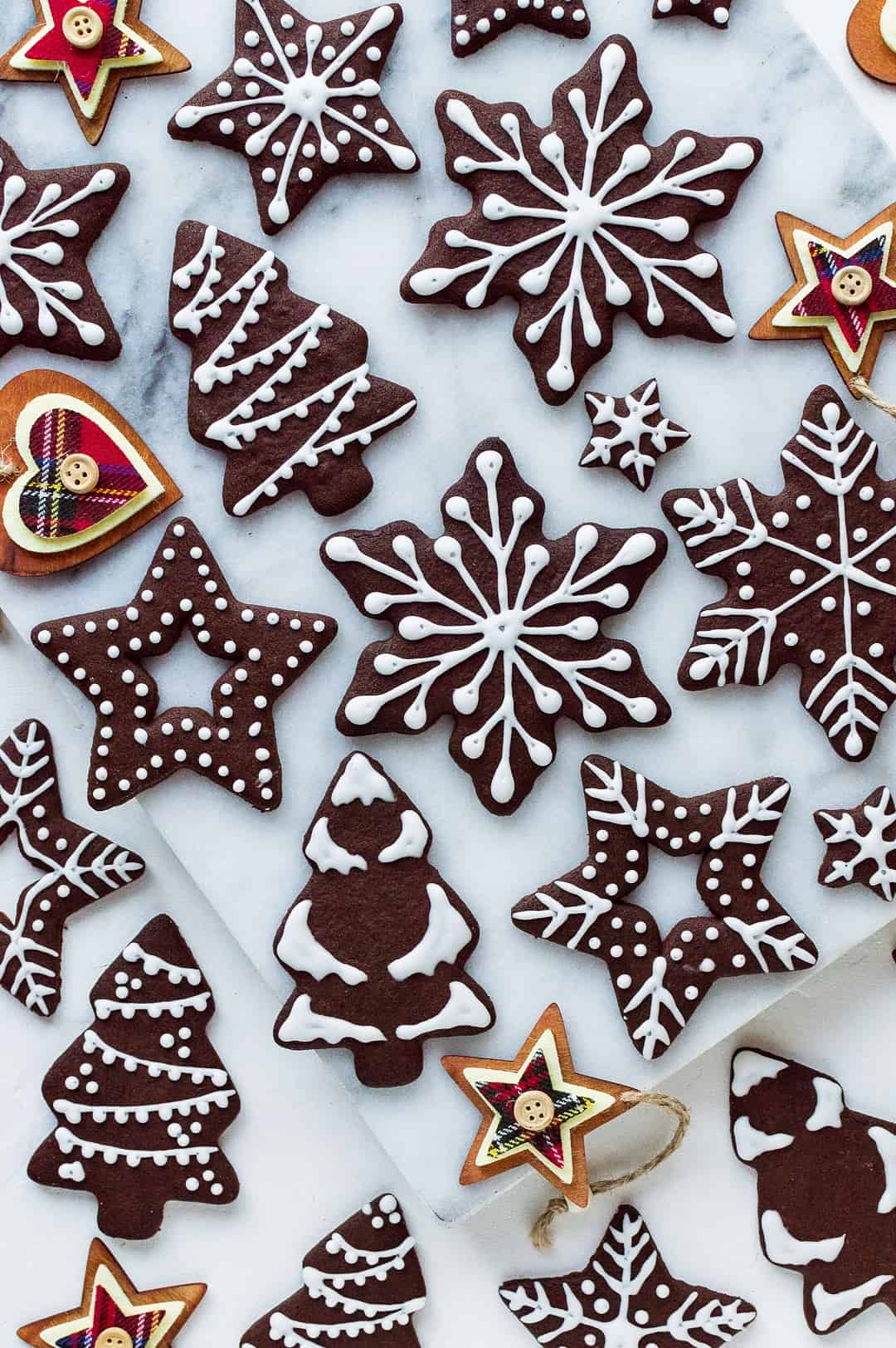 Top down photo of chocolate gingerbread cut-out cookies decorated with white royal icing.