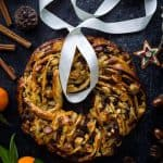 A top down shot of a braided bread wreath filled with fruit mince, marzipan and apple; surrounded by clementines, spices and Christmas decorations
