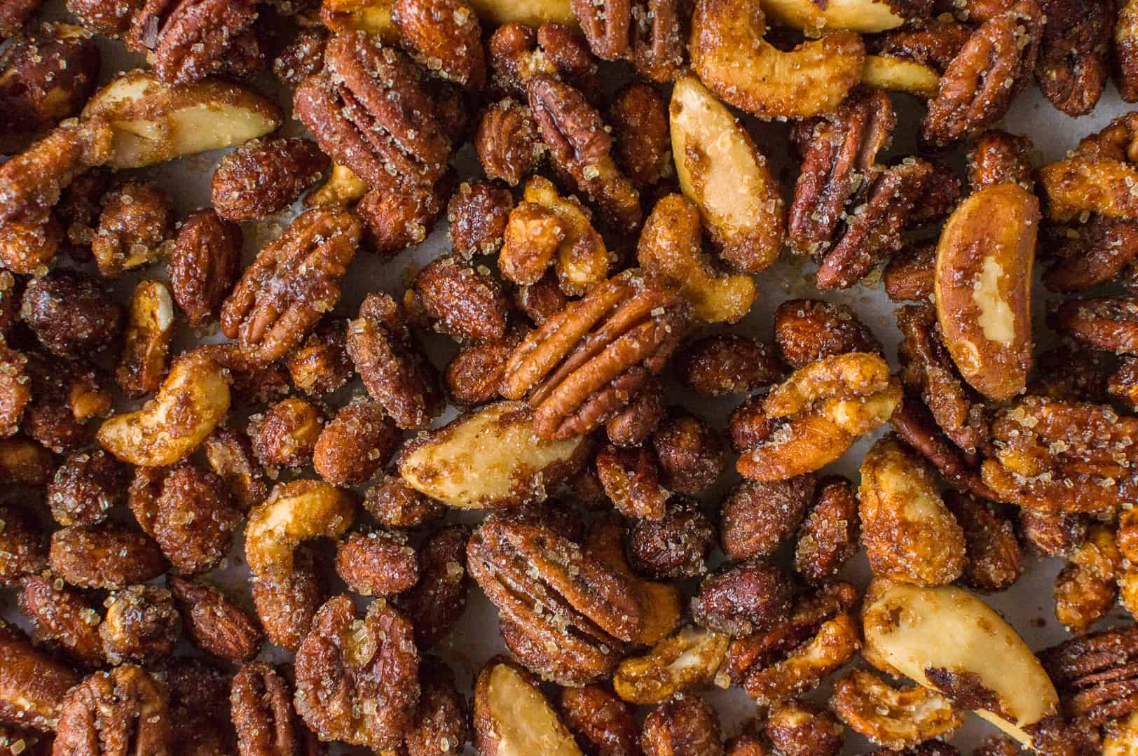 Close up of golden, sugar encrusted roasted pecans, cashews, brazil nuts, almonds and hazelnuts.