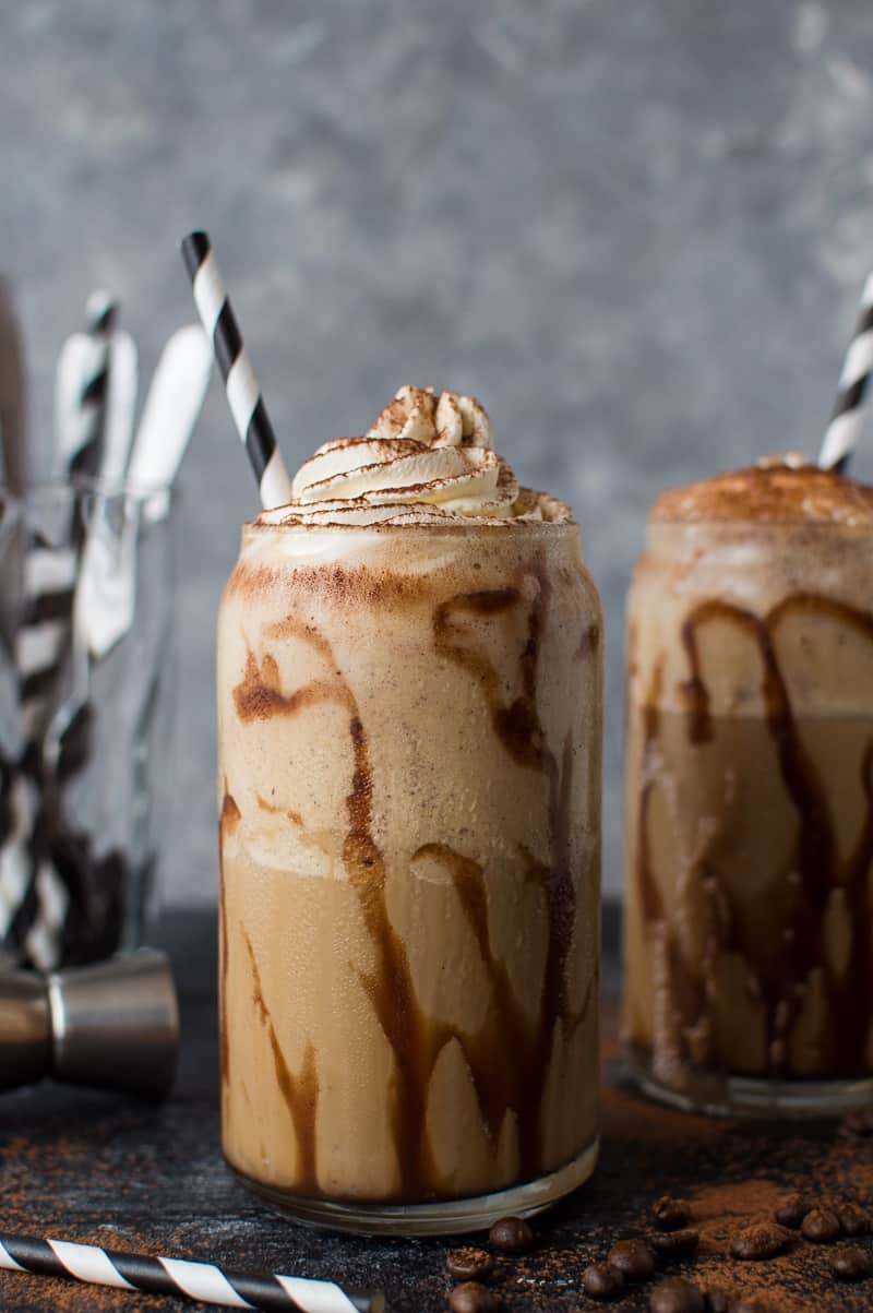 Photo of two glasses of coffee Kahlua milkshakes with chocolate sauce, whipped cream and paper straws on a dark background.