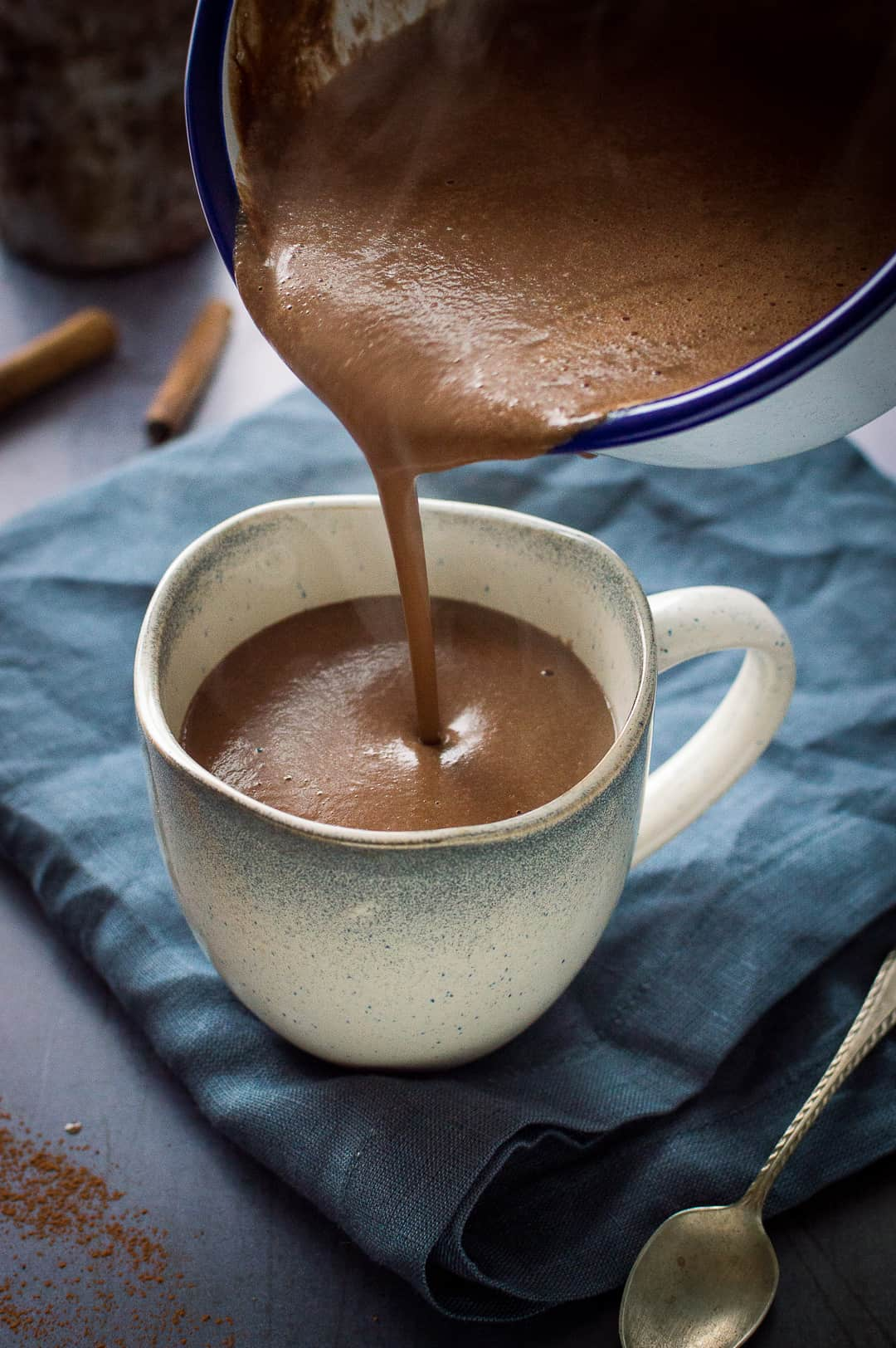 Thick, creamy vegan gingerbread hot chocolate being poured into a grey mug.
