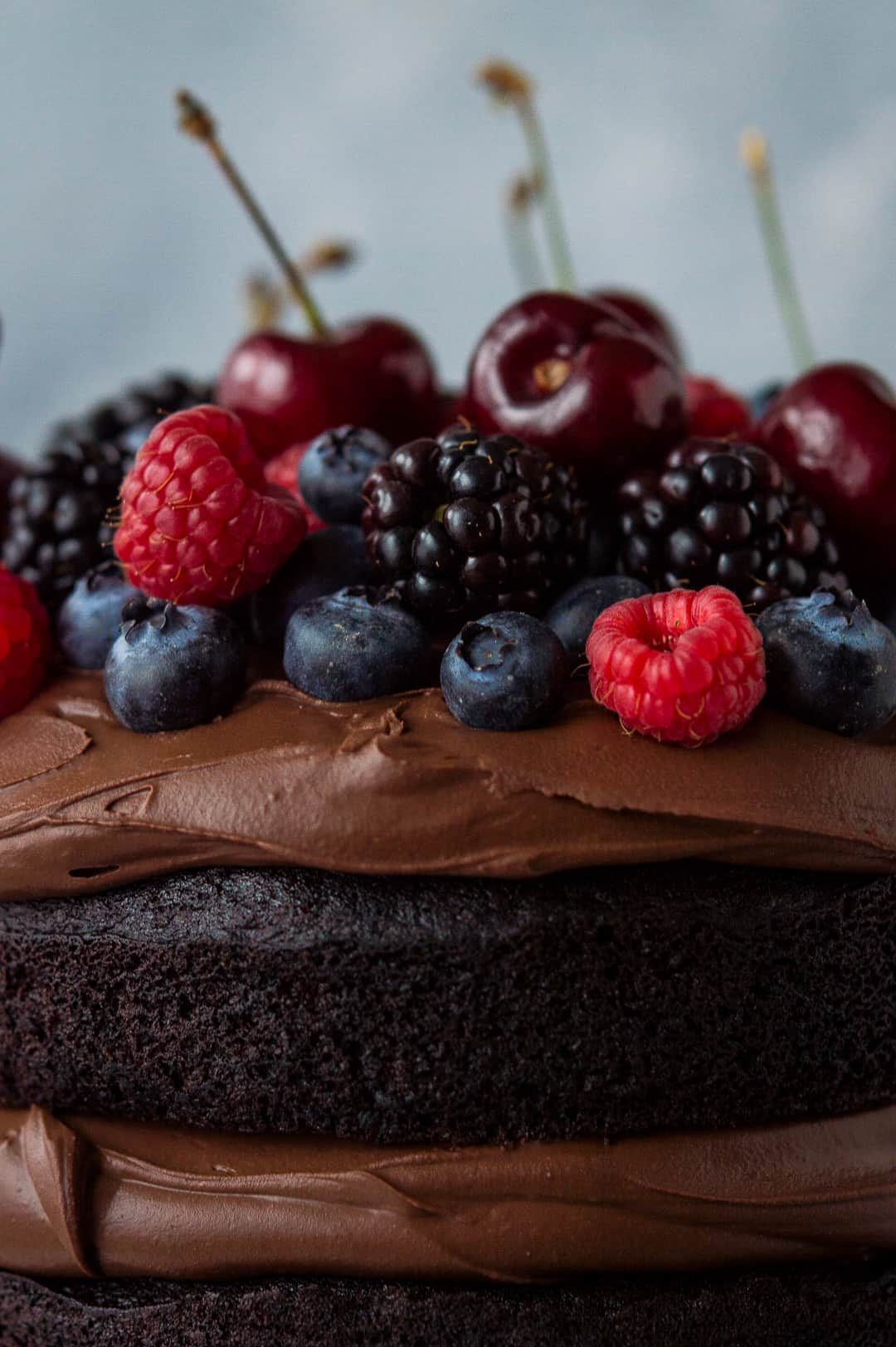Close up of berries on top of vegan chocolate cake with vegan ganache