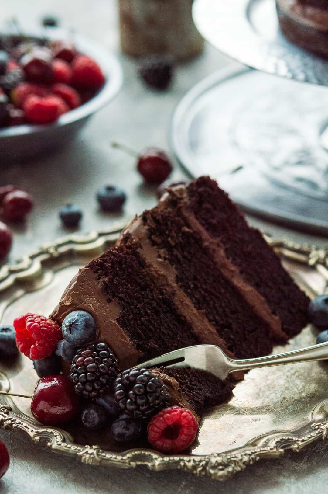 A slice of vegan chocolate fudge cake with coconut milk ganache topped with berries on a pewter plate.