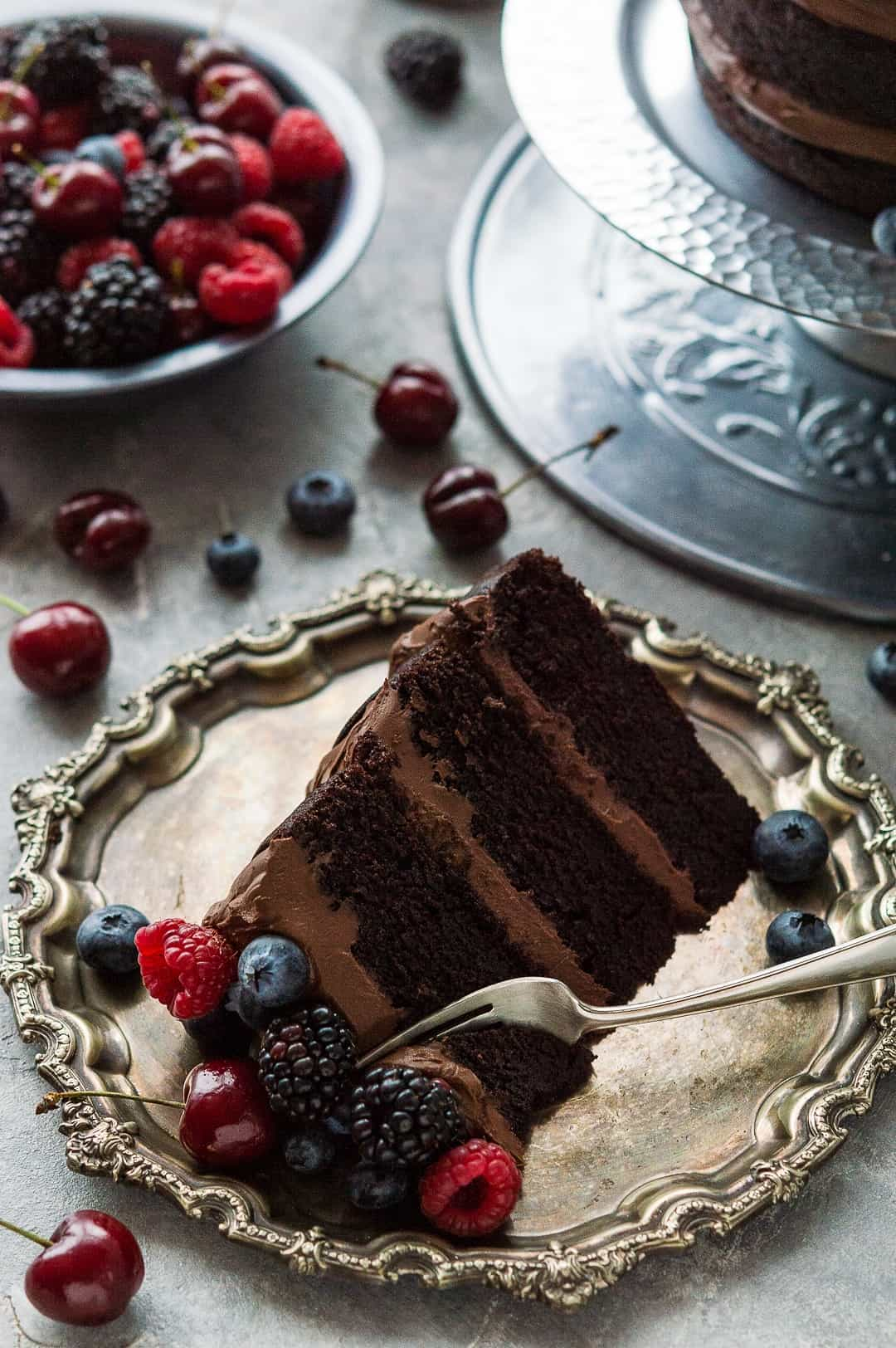 Slice of easy vegan chocolate cake with vegan ganache on a pewter platter with fresh berries.