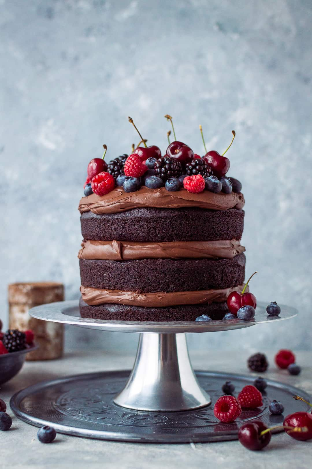 Vegan chocolate fudge cake with coconut milk ganache and fresh berries on a silver cake stand.