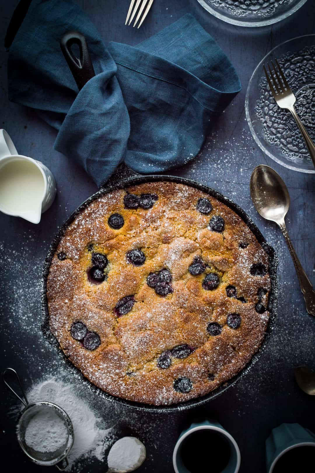Blueberry cornmeal cake cooked in a cast iron skillet on a dark background.