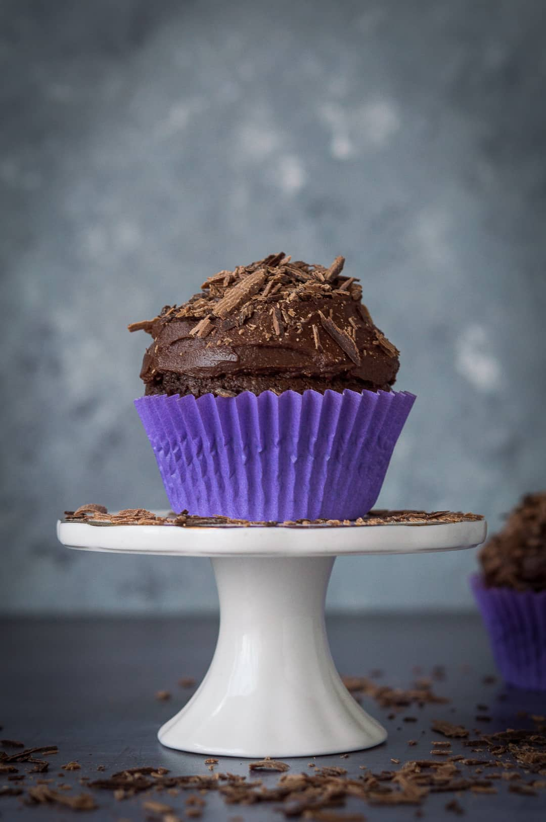 A vegan chocolate cupcake on top of a mini cake stand scattered with chocolate shavings.