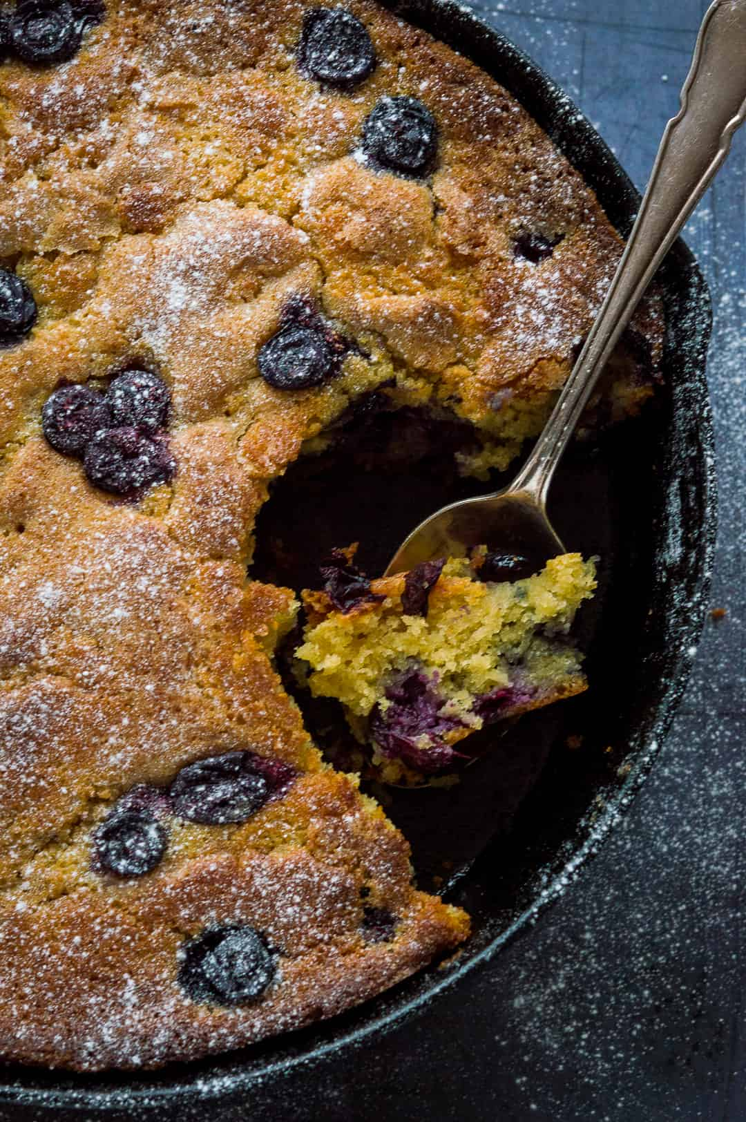 A close up of blueberry cornmeal skillet cake, served straight from the skillet