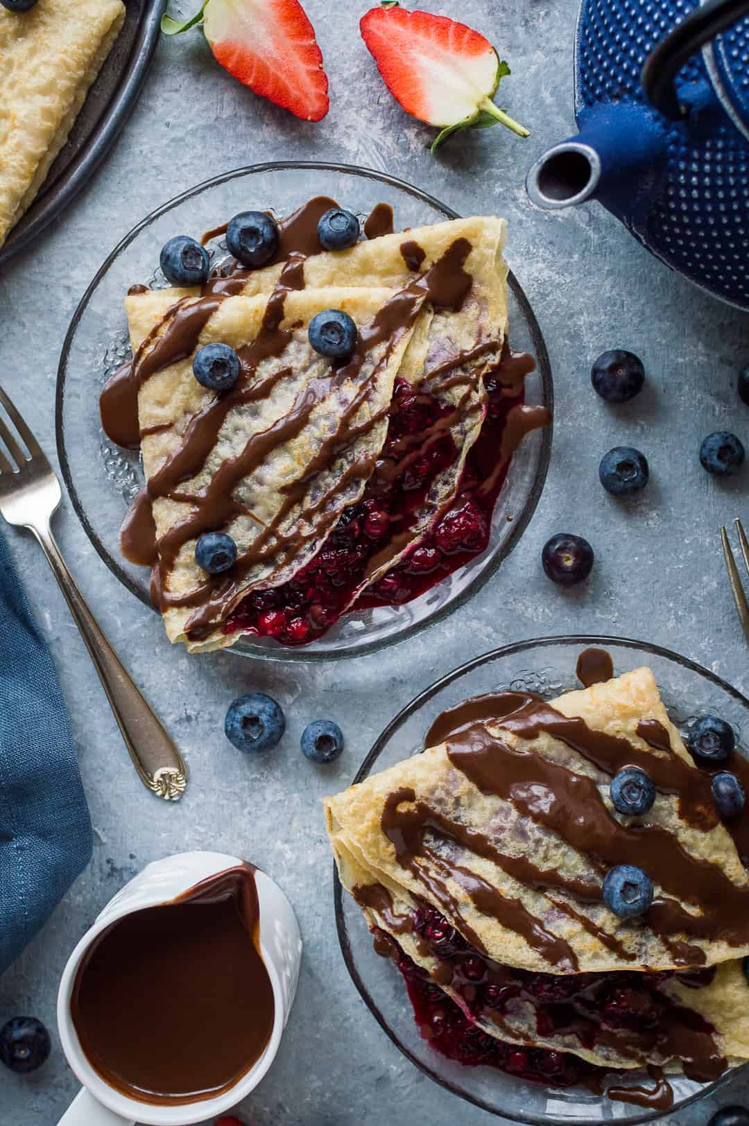 Two glass plates of pancakes filled with berry compote and drizzled with chocolate sauce and blueberries.