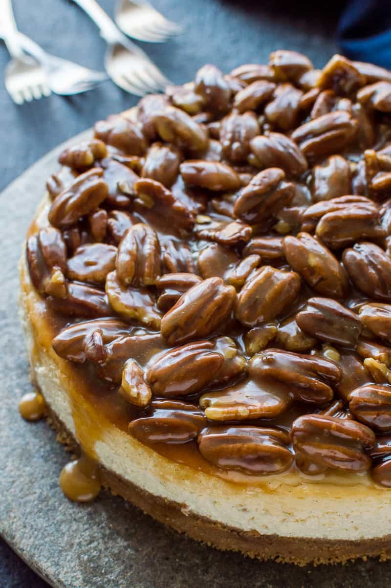 Side shot of baked vanilla cheesecake topped with caramel pecans on a dark background.