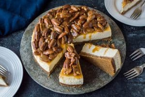 Baked vanilla cheesecake with biscuit base topped with pecans in a caramel sauce.