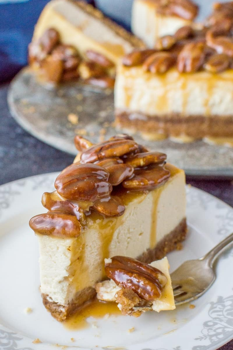 A slice of pecan pie cheesecake - baked vanilla cheesecake topped with caramel pecans.