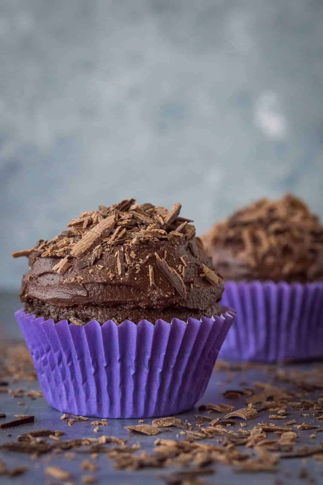 Two vegan chocolate cupcakes in purple cake cases.
