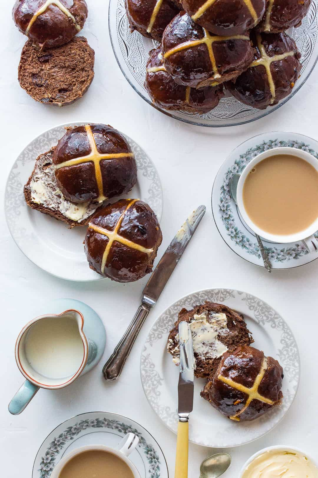 Chocolate orange hot cross buns on a white surface with butter and cups of tea.