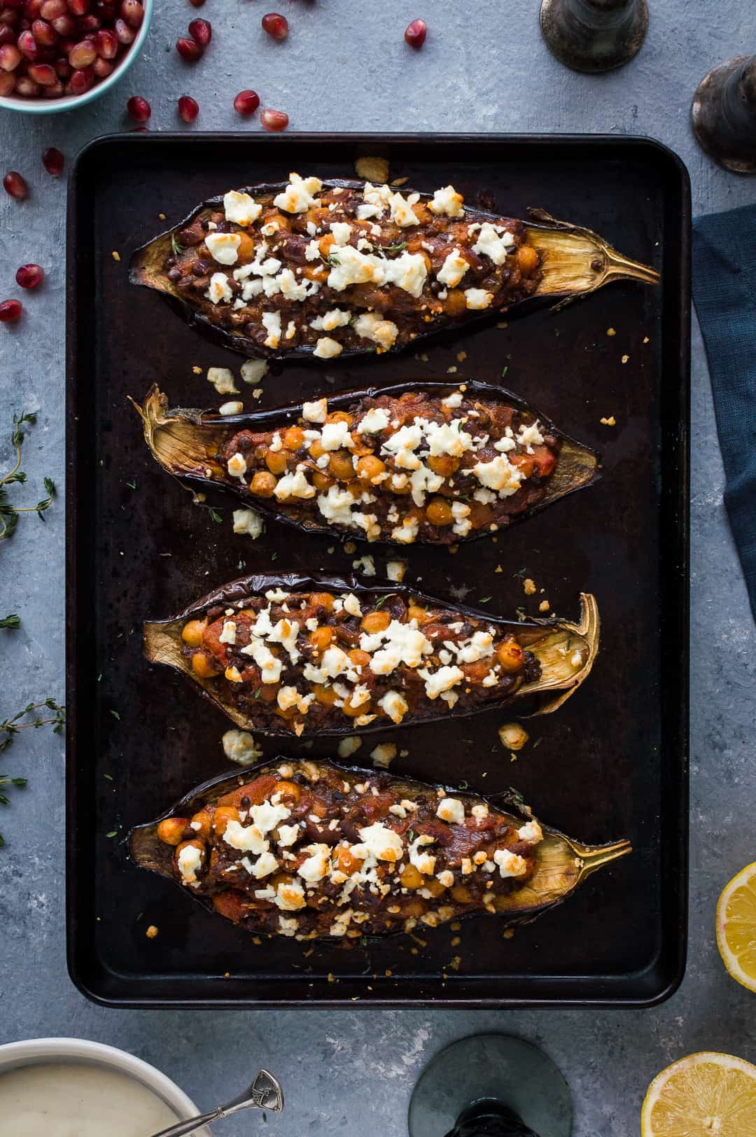 Roasted aubergines stuffed with chickpeas and lentils toppedwith feta on a black baking tray.
