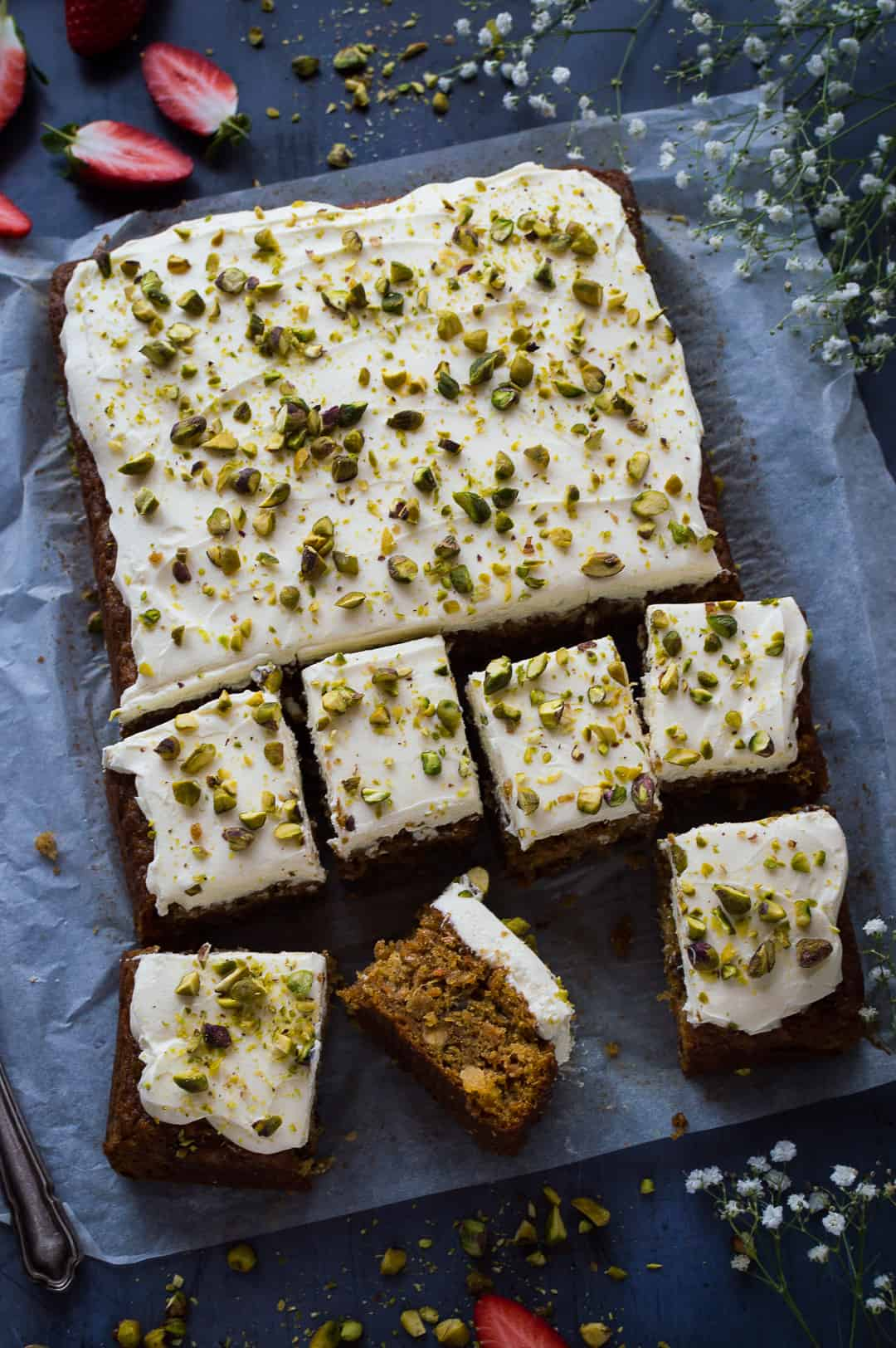 carrot, pineapple and pistachio cake topped with cream cheese frosting sliced into squares