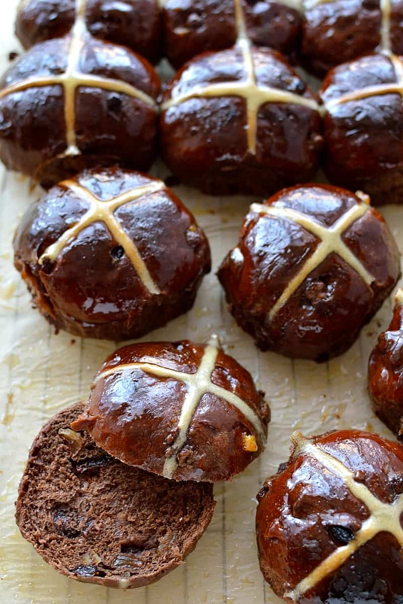 Close up of chocolate orange hot cross buns flavoured with cocoa powder, chocolate chips, candied peel and orange zest.