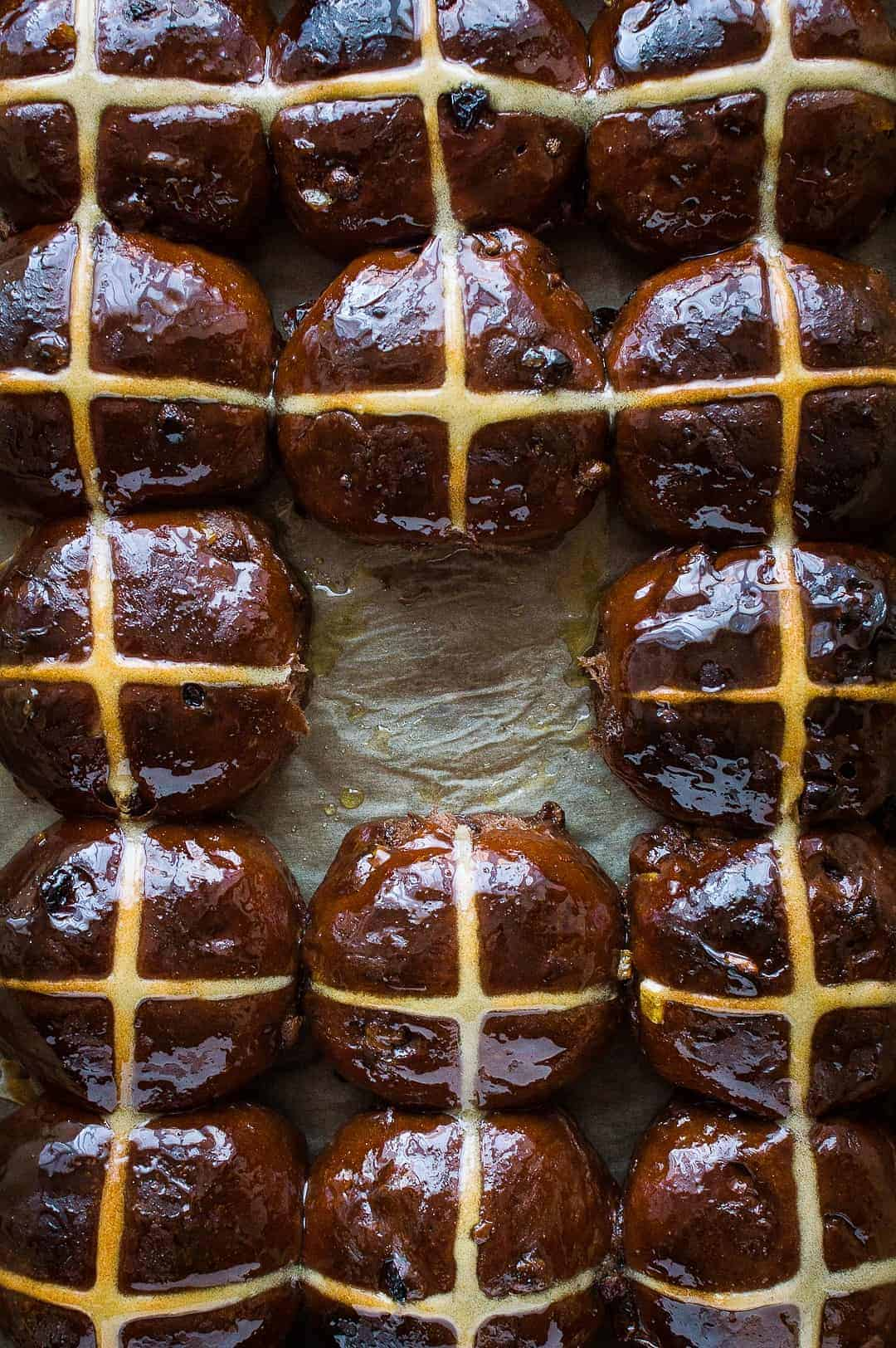 Top down shot of chocolate orange hot cross buns with the middle one removed.
